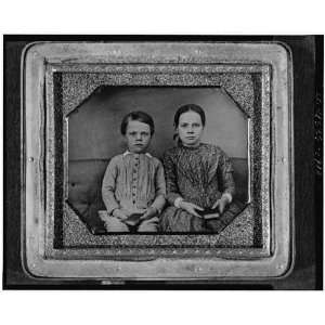 Group of an unidentified boy,girl,on upholstered bench,holding
