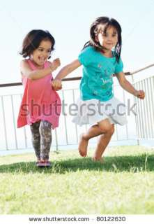 Full Length Of Cute Little Girls Having Fun In Park Stock Photo